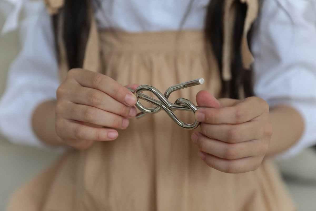 crop little girl holding metal knot teaser