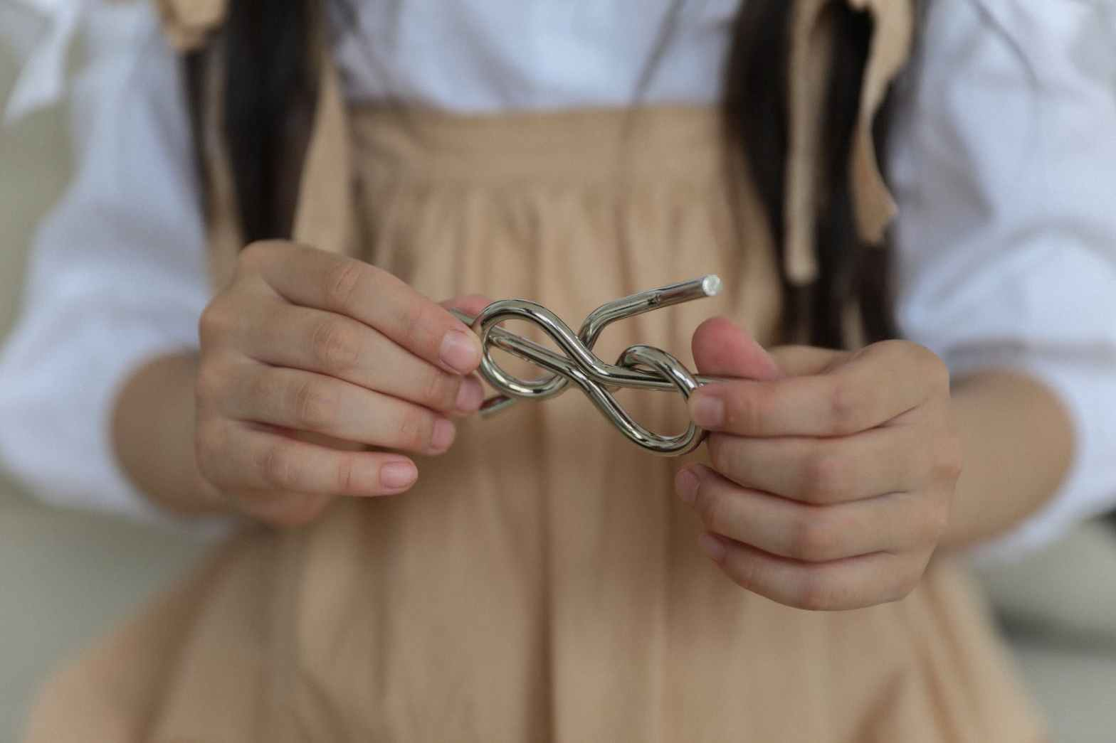 crop little girl holding metal knot teaser