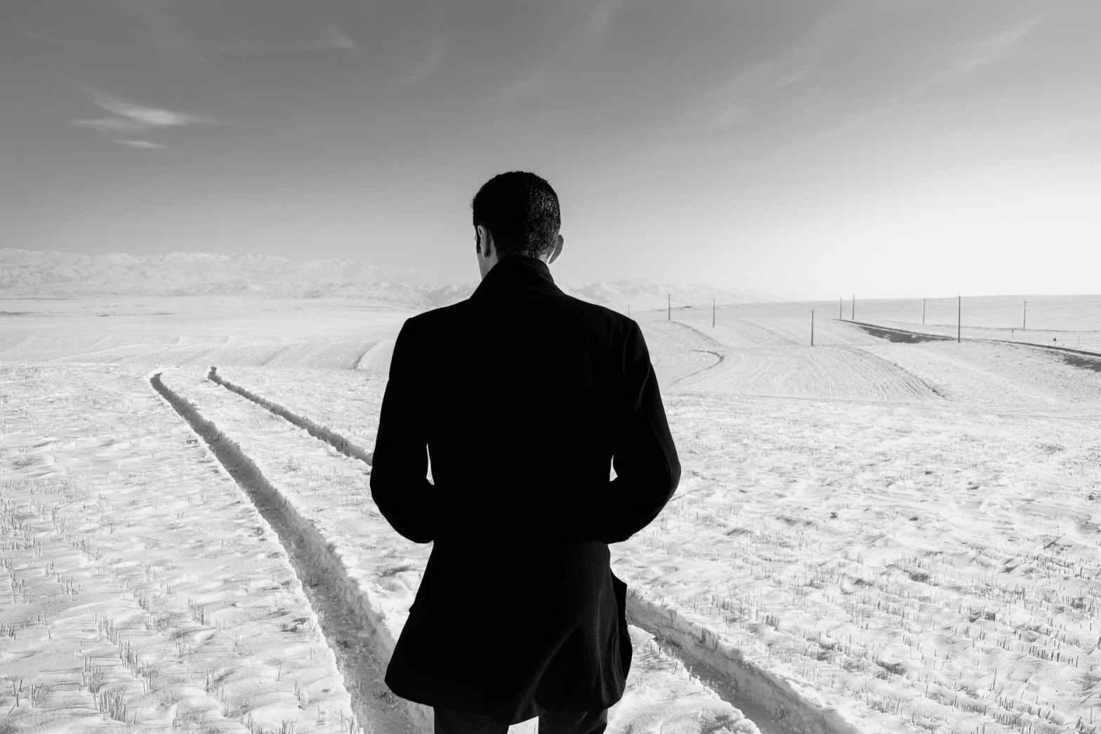 unrecognizable man in snowy field