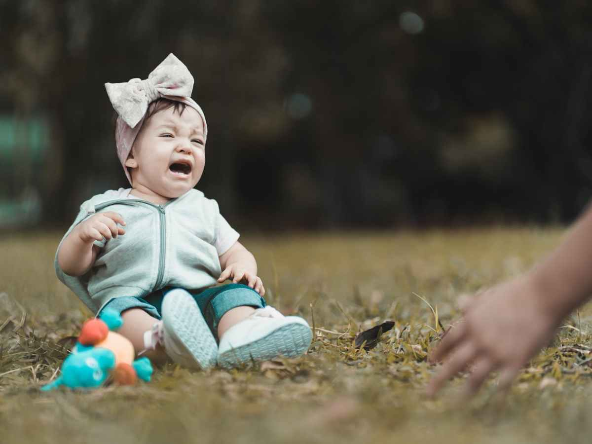 little girl crying and sitting on meadow