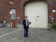 K800_Jörg Rostek mit einer grünen Zeitung vor dem Eingang der JVA Münster