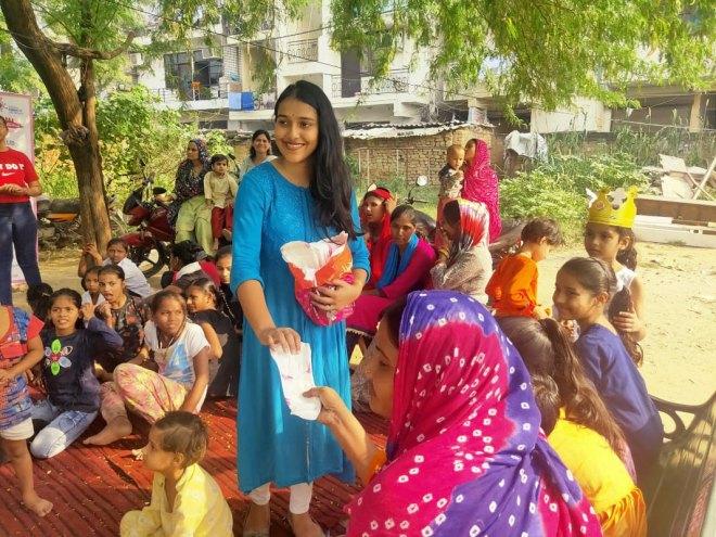 RAC Sri Aurobindo College president Sakshi Raman distributing sanitary pads to beneficiaries.
