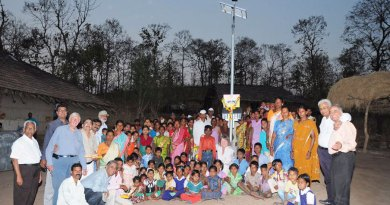 Rotarians and villagers standing under a newly installed solar street lamp.