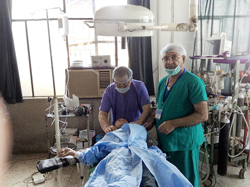Medical Director of RAHAT PDG Dr R S Parmar (right) operating on a patient.