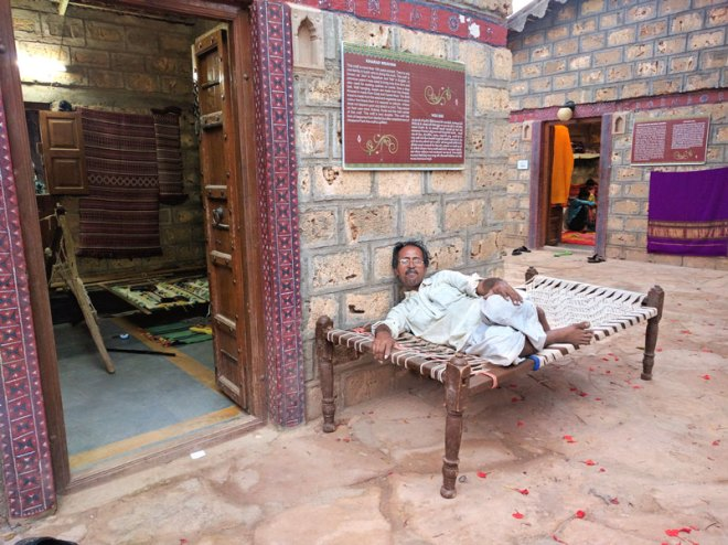 A Kharad artisan takes a break from the strenuous weaving.