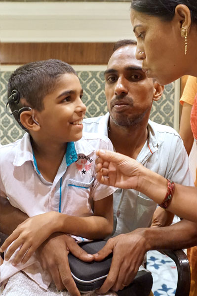 Young Nitin in conversation with his parents after his hearing has been restored, thanks to the cochlear implant.
