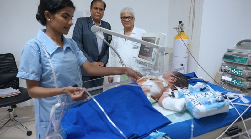 Dr Suresh Rao, accompanied by D 3141 DG Gopal Mandhania examines an infant after surgery.