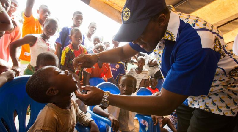 A Rotarian inoculates a child with polio vaccine during a welcome ceremony kicking off a National Immunisation Day (NID) in the village of Messikro, Cote d'Ivoire.