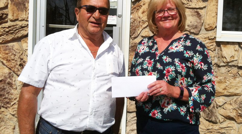 Andre Cougias from Acropole presented Wendy Bourque with a $50,000 donation for the splash park the Westville Rotary is building.
