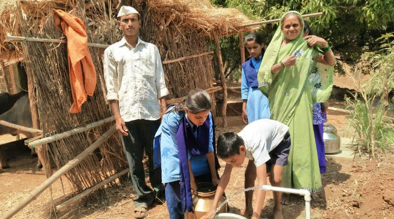 A family collects water from a tap at their doorstep.