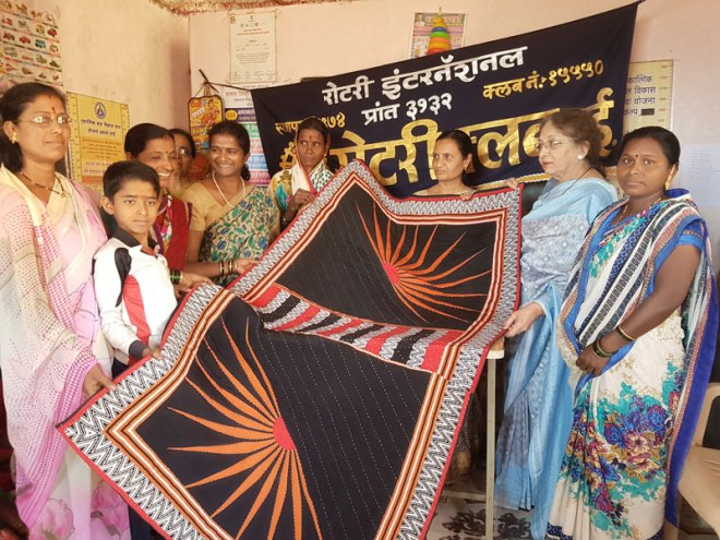 Villagers present a handwoven quilt to Rtn Swati Herkel (fourth from left) and PDG Meena Patel of D 6650 (second from right).