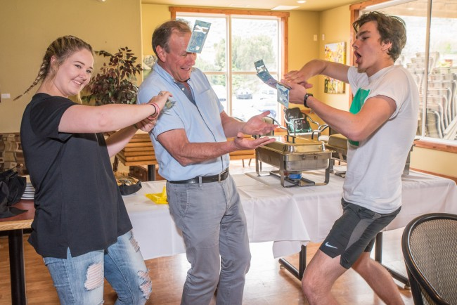 Lukáš Kršek, right, from the Czech Republic, showered Trevor Caldecott with $50 in cash from his 50-50 winnings and Olivia Greenwood-Jack, left, from Australia did the same with her $45 winnings. The Rotary exchange students made the gesture of support after hearing Caldecott's presentation about the oppressed Dalit people in India.