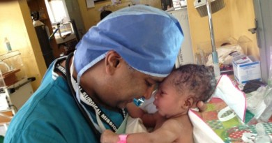 Riverhead surgeon Rajesh Patel, with a baby he helped deliver in Brazil. Courtesy photo: Rajesh Patel.