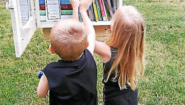 Two young visitors check out the book selections at Bedford Elementary School's recently installed Little Free Library.
