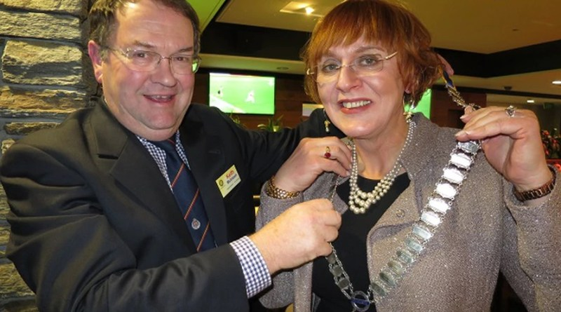New Queenstown Rotary president Monica Mulholland receives the chains of office from outgoing president Keith McIntosh. Photo: Mountain Scene