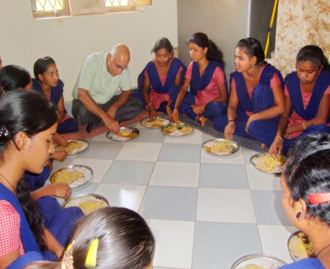 Subroto Bagchi shares a meal with the trainees at a sewing machine operation centre.