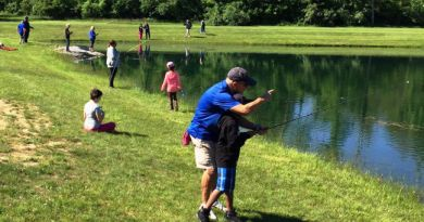 Charlie Zammit helps one of the the students reel in a fish. Photo: Southgate Rotary