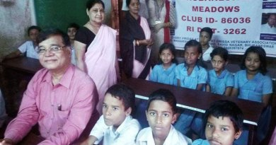 PDG Aswini Kar with students seated on dual desks provided by the club.