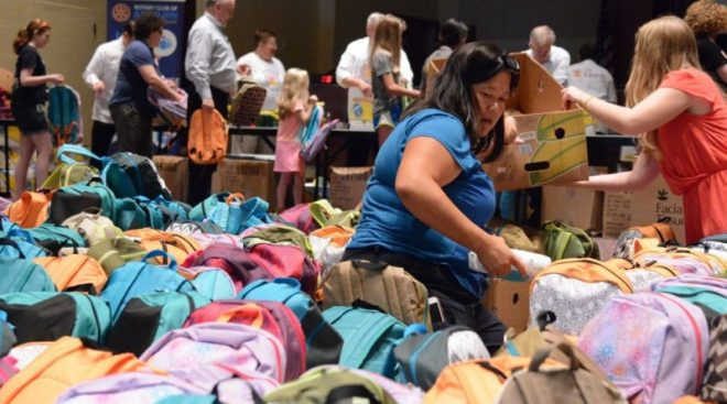 Volunteers pack hundreds of donated backpacks to send to Loudoun elementary schools. Photo: Renss Greene, Loudoun Now