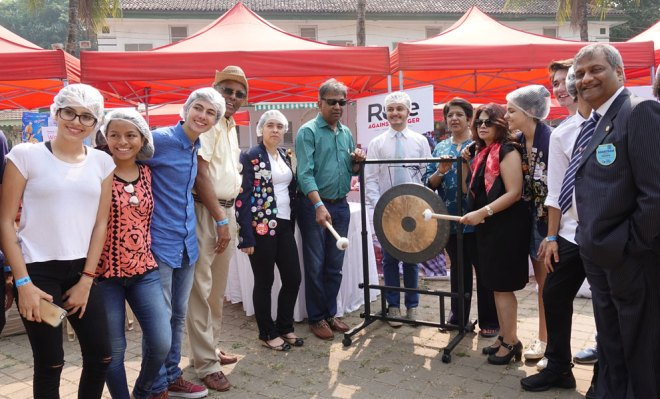 DG Prafull Sharma and spouse Vidyottama Sharma strike the gong to mark the beginning of the meal packaging programme.