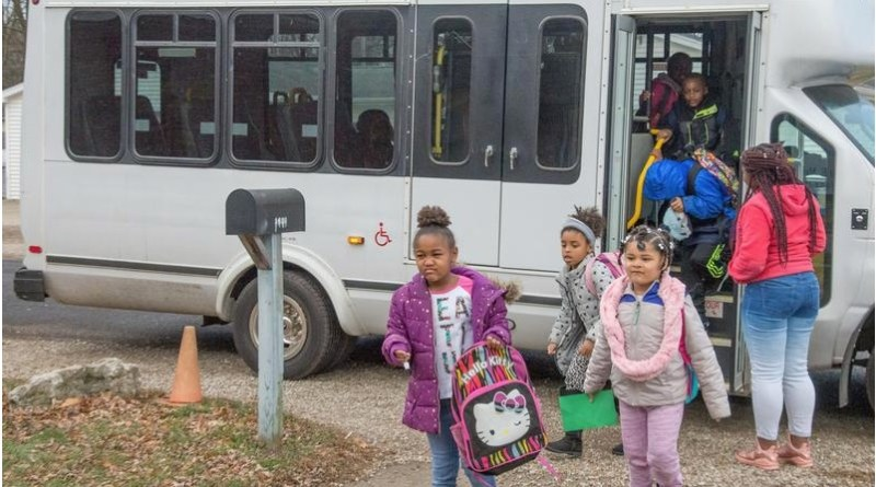 Activity leader Andrianna Moore greets students as they get off the bus at the Urbana NeighboUrhood Connections Centre. Photo: Robin Scholz/The News-Gazette
