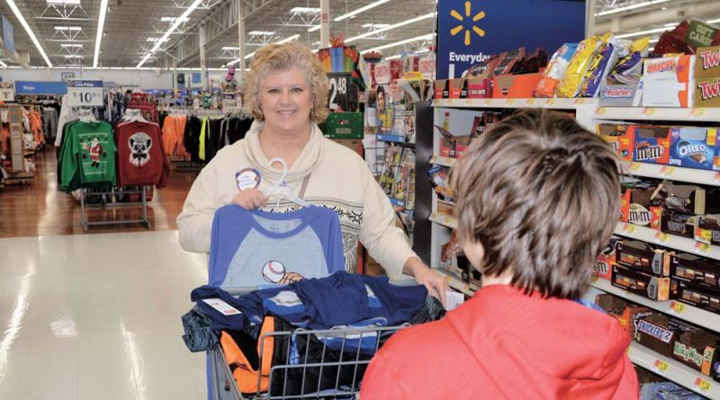 Volunteer Lisa Rogers stands in line with a student from Fairview-Marguerite Elementary School during the Morristown AM Rotary Club's annual shopping trip. Over 100 children were able to pick out Christmas gifts during the event.