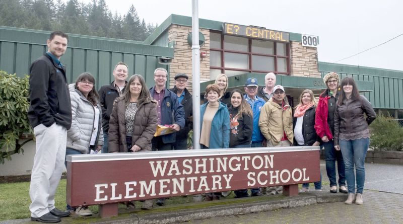 Members of the Twin Cities Rotary Club, school faculty and assorted volunteers pose for a photo in front of Washington Elementary School on Friday afternoon before heading out to delivery $20,000 worth of donations to families in Centralia.