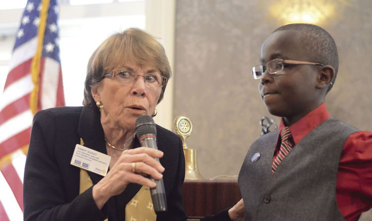 Edina Rotarian Sandy Schley interviews Moses Mwaura in front of Rotary Club members at the group's Dec 7 meeting. Touched by her initial encounter with the now-13-year-old, Schley helped initiate the club's project to fix Moses' eyes. Photo: Andrew Wig/Sun Current