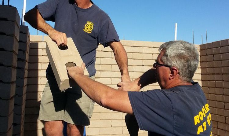 Rotarian Tom Hartrick hands Rotary Club of the Delta  President Mike Green, seen on the ladder, a brick to place on the expanding structure that will become a family's home in San Luis Rio Colorado, Mexico. The two were part of a Rotarian effort to help bring relief to this poverty-torn area. Photo: Mike Green