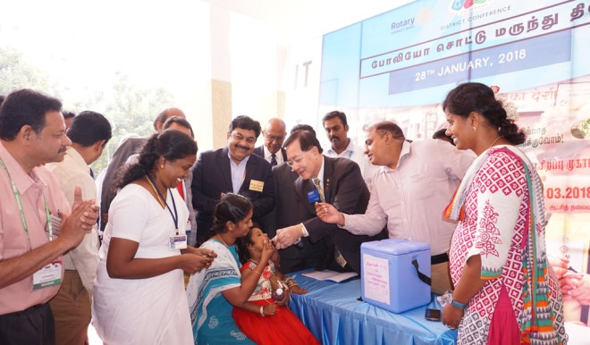 PRID Frederick Lin giving polio drops to a child. DGN Dr A Zameer Pasha, PDG P V Parthasarathy and Conference Secretary M C Saanthosh are also in the picture.