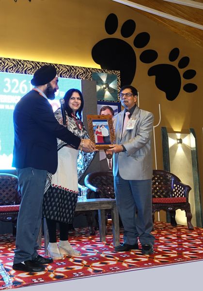 DG Harjit Hura honours PDG Subhash Sahu at the District conference. Also seen is his spouse Rani.