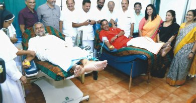 An imam and a thantri donate blood as Rotarians look on.