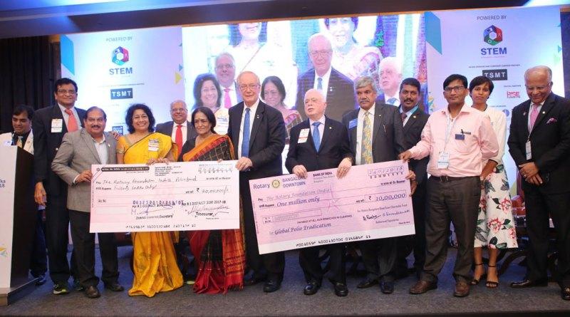 TRF Trustee Chair Paul Netzel and Trustee Sushil Gupta receive the cheques from PDG Madhura Chatrapathy, DG Asha Prasanna Kumar, Rtn Prasanna Kumar and Srikanth M Chatrapathy at the CSR Conclave. Also seen: DGN Sameer Hariani (far left), PRID Manoj Desai, PDG (D 3131) Vinay Kulkarni, Rotarians Illavarasan, Prashanth, Shoba and PP Ramdas.