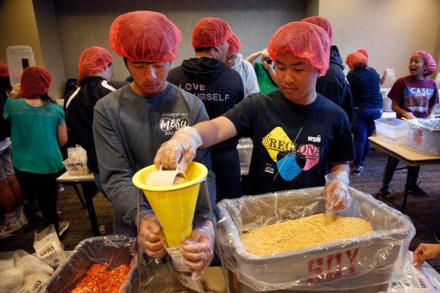 Volunteers An Le and George Luna pack meals at the Rotary club's Community Day event in a Marriott Hotel convention room in San Jose, California. Photo: Karl Mondon/Bay Area News Group
