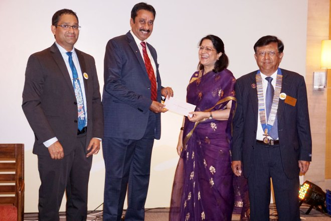RC Madras President-nominee Dr Vijaya Bharathi presents a cheque to DG R Srinivasan as President P N Mohan (right) and Nikhil Raj (left) look on.