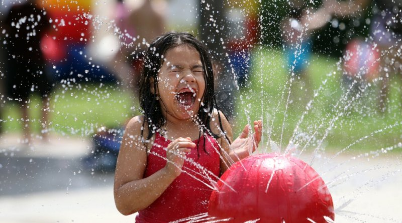 A young girl squeals in delight as water shoots from one of the fountains at the Rotary Island splash pad at Rock Creek Park on Saturday. Photo: Jessica Brown
