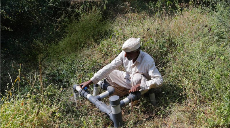 A farmer at the pipe connecting to the drip irrigation system.