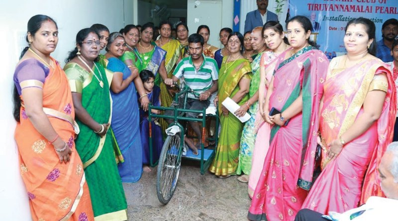 A tricyle being given to a beneficiary.