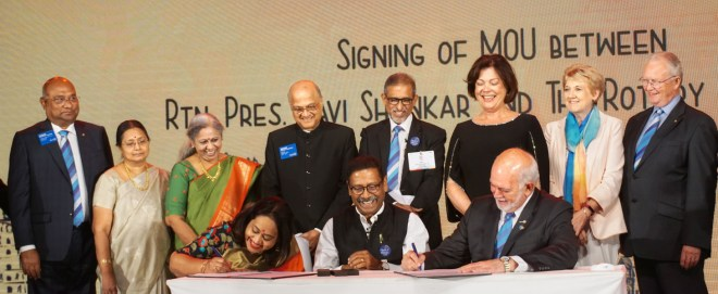 RI President Barry Rassin signs an MoU with RC Bangalore Orchards President Ravi Shankar and spouse Paola in the presence of (from L) RID C Basker, Mala, Anita Hari, TRF Trustee Gulam Vahanvaty, D 3190 DG Suresh Hari, Esther Rassin, Alison Webb and TRF Trustee Mike Webb.