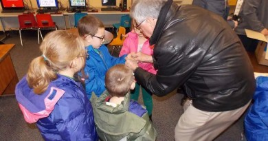 Dr James Evans of the Rotary Club of Bradford cuts tags off of new coats provided to children at George G Blaisdell Elementary School through the Operation Warm project. Photo: Kate Day Sager