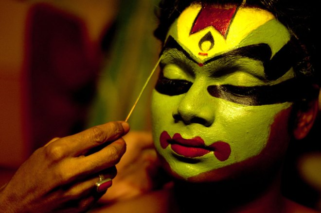 An artist getting dressed up for a Kathakali performance.