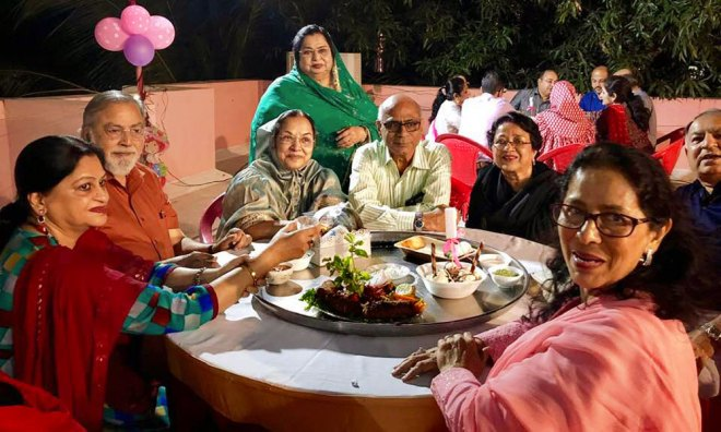 A Bohra gathering enjoys traditional food from a large thaali.