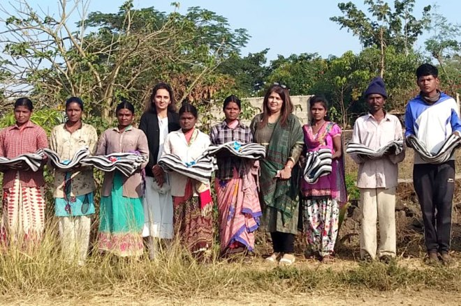Rotarians distribute bedsheets to field workers.