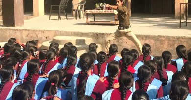 A police personnel demonstrates karate  to students in a school.