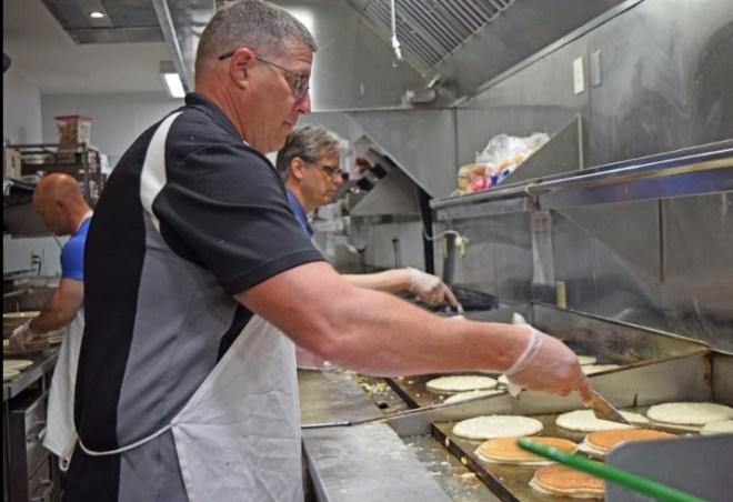 Rotarian Chris Harris flips rows of pancakes while volunteering for the Toad Suck Daze Pancake Breakfast. Photo: Marisa Hicks