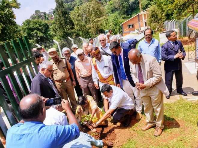 Nilgiris District Collector Innocent Divya plants a sapling in the crematorium campus.
