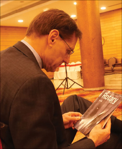 RI General Secretary Hewko reading a copy of Rotary News.