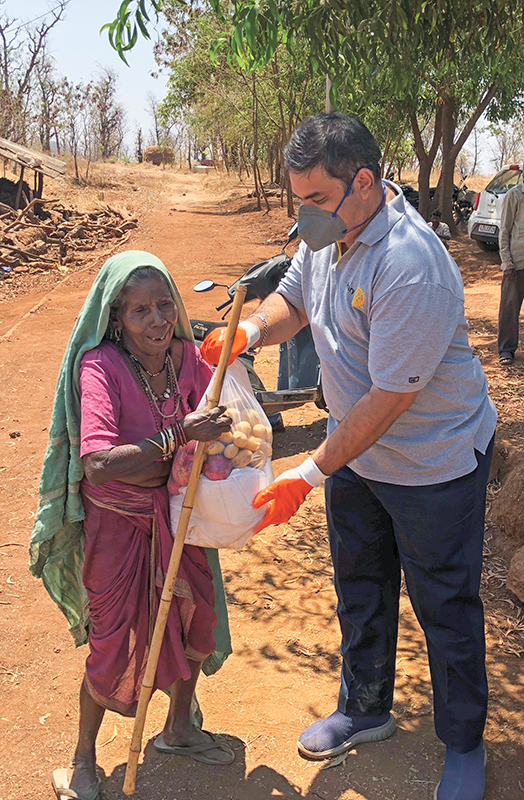 Rtn Chirag Gandhi helping a tribal woman with some vegetables and groceries.