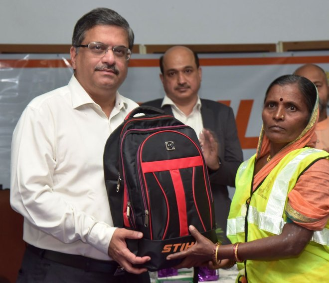 Abhijit Joag gives a safety kit to a sanitation worker as Parind Prabhudesai, MD, Andreas STIHL India, looks on.