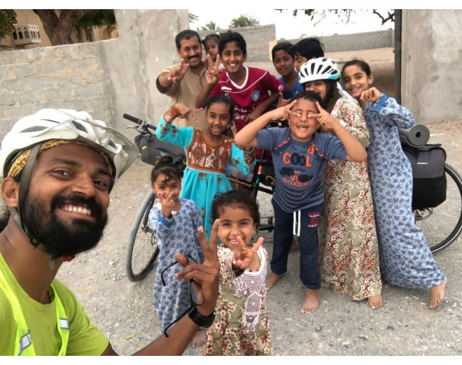 People pose with Naresh Kumar and his bicycle in India.